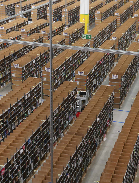 BBVA, OpenMind. Technological Progress and Potential Future Risks. WEst. Workers walk among shelves lined with goods at an Amazon warehouse, in Brieselang, Germany. Germany is online retailer Amazon's second largest market after the USA.