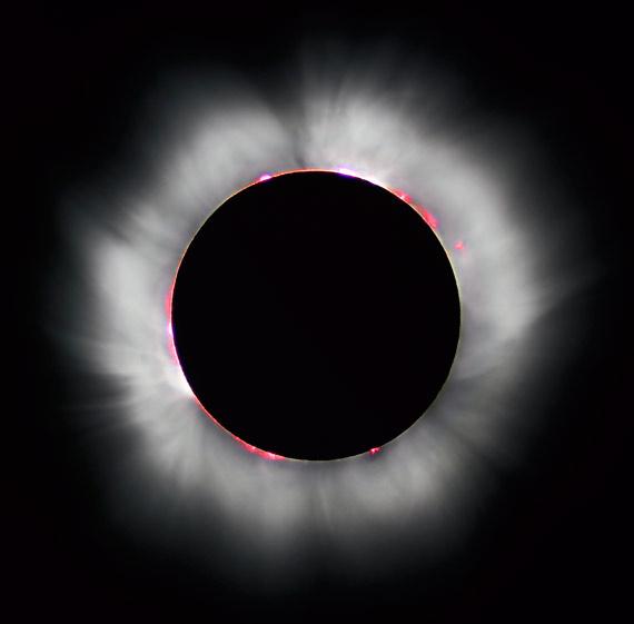 Eclipse total de Sol en Francia (1999). La Luna deja ver protuberancias solares (en rojo) y filamentos de la corona (en blanco). Crédito: Luc Viatour