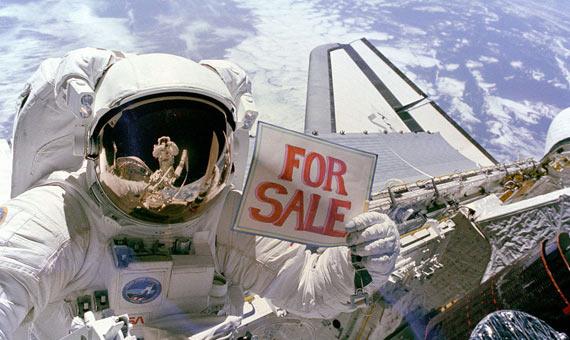 """El astronauta Dale A. Gardner sujeta el cartel de """"Se vende"""" en referencia a dos satélites recuperados. Crédito: NASA"""