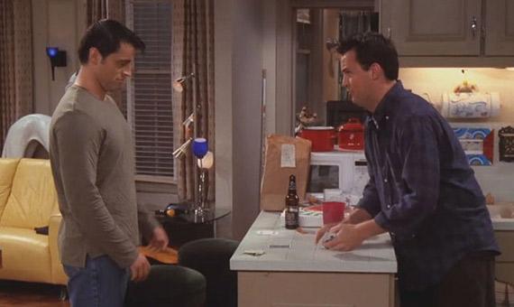 Chandler enseña a Joey cómo jugar a CUPS. Crédito: NBC