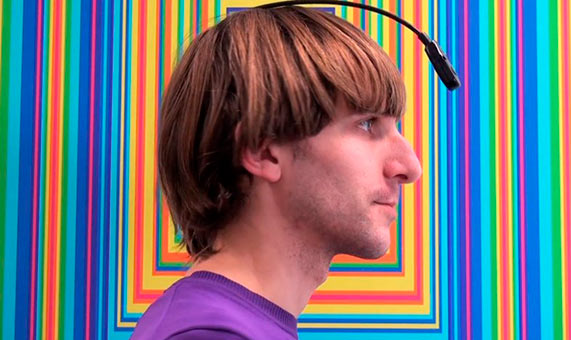 Neil Harbisson with his antenna in front of one of his pieces of work