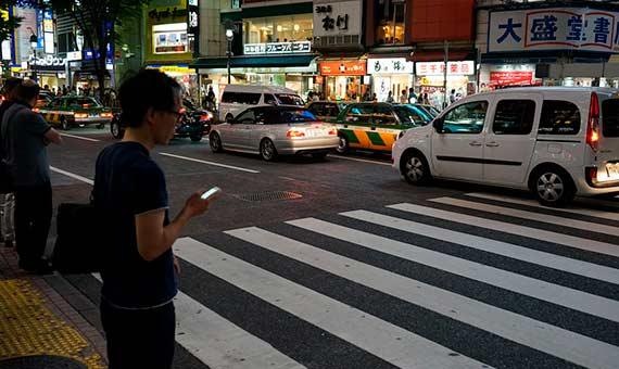 Crossing the street while watching the smartphone involves danger to both pedestrians and drivers. Credit: Tonnoro