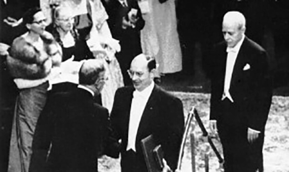During the Nobel awards ceremony in 1956, greeting King Gustav VI Adolf of Sweden. Behind him, Walter Brattain, another of the prizewinners.