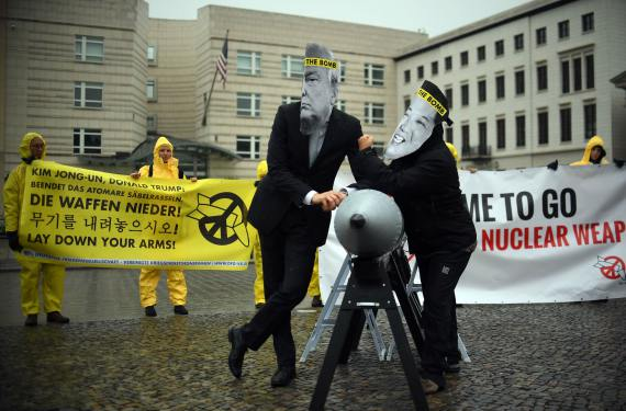 BBVA-OpenMind-Libro 2018-Perplejidad-Andrews-Armas-Nucleares-Activists of the NGO 'International Campaign to Abolish Nuclear Weapons (ICAN)' wear masks of US President Trump and the Democratic People's Republic of Korea Kim Jon-un while posing with a mock missile in front of the Democratic People's Republic of Korea embassy in Berlin in September of 2017.