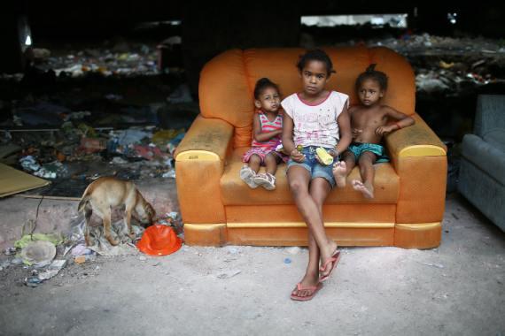 Unos niños miran a la cámara en un área empobrecida en el complejo de Yegua, una de las favelas más grandes de Río de Janeiro, Brasil. BBVA-OpenMind-Libro 2018-Perplejidad-Conconi-Viollaz-Favelas-pobreza