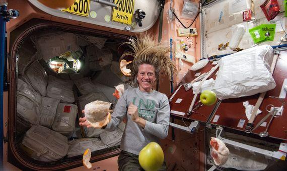 La astronauta Karen Nyberg, fotografiada flotando entre piezas de fruta en la Estación Espacial Internacional. Crédito: NASA.