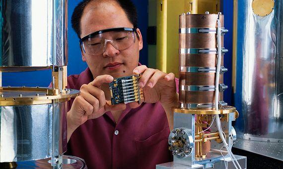 En la imagen, un físico del Instituto Nacional de Estándares y Tecnología sostiene un circuito que se utiliza para amplificar las señales de un detector de fotones. Crédito: Geoffrey Wheeler.