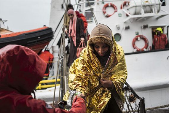BBVA-OpenMind-Ilustracion-Michelle-Baddeley-Economia-conductual_Un voluntario de la ONG española Proactiva Open Arm ayuda a desembarcar a una inmigrante, a la que han rescatado a 20 millas de las costas libias, en el puerto de la ciudad italiana de Crotona, marzo de 2017