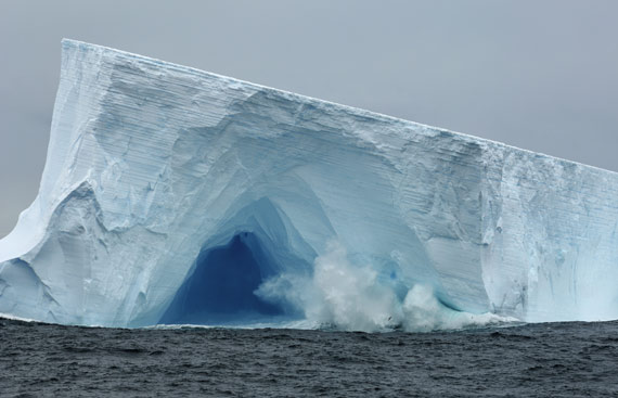 Antarctica, Scotia Sea, near South Georgia, waves crashing on tabular iceberg with cave