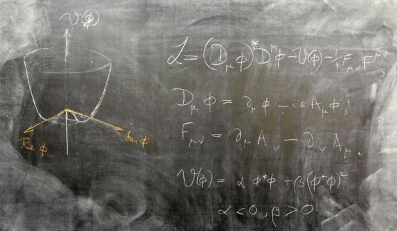 Pizarra con la ecuación del mecanismo de Higgs que explica cómo el campo Higgs confiere masa a otras partículas que interactúan con él. Esta interacción la hace posible la partícula elemental conocida como el bosón de Higgs