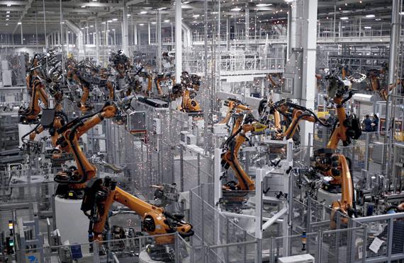 BBVA-OpenMind-ilustración-Joanna-J-Bryson-la-ultima-decada-y-el-futuro-del-impacto-de-la-IA-en-la-sociedad-Robots soldando componentes para vehículos en la planta de ensamblaje de Bayerische Motoren Werke AG (BMW) en Greer, Carolina del Sur, mayo de 2018