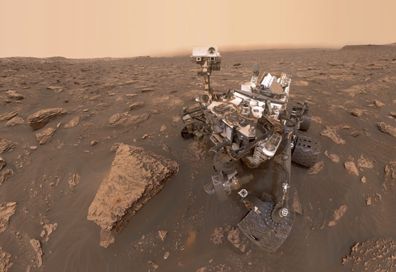 "BBVA-OpenMind-ilustración-Martin-Rees-La-ultima-decada-futuro-de-la-cosmologia-y-astrofisica-A self-portrait by NASA's Curiosity rover taken on Sol 2082 (June 15, 2018). A Martian dust storm has reduced sunlight and visibility at the rover's location in Gale Crater. A drill hole can be seen in the rock to the left of the rover at a target site called ""Duluth"""