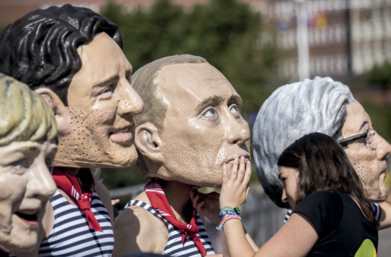 BBVA-OpenMind-ilustración-gonzalez-nueva-ilustracion-digital_papel-industria-financiera_Oxfam activists wearing masks with the faces of political leaders (in the photo: Vladimir Putin and former Italian prime minister Paolo Gentiloni) demonstrate at a G20 meeting in Hamburg, Germany, in July 2017
