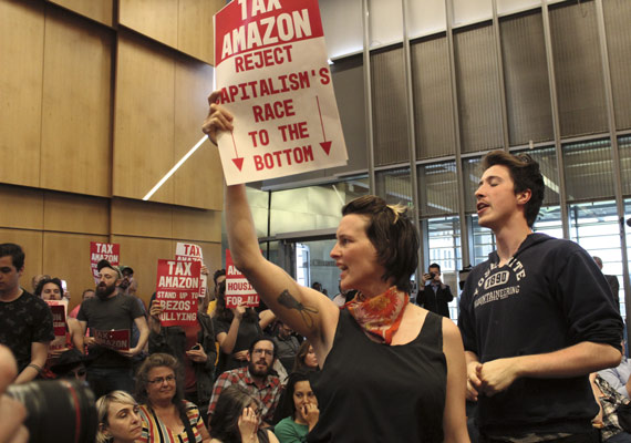BBVA-OpenMind-ilustración-gonzalez-nueva-ilustracion-digital_papel-industria-financiera_At a municipal vote in Seattle, various demonstrators hold signs demanding that locally based multinational corporations, such as Amazon, be taxed to combat rising housing prices