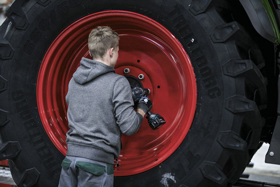 An employee secures the rear wheel of a tractor inside the Fendt GmbH agricultural machinery factory in Marktoberdorf, Germany