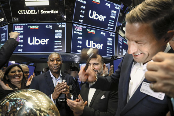 BBVA-OpenMind-Jamie-Woodcock-Efectos-de-la-gig-economy-2-Uber co-founder Ryan Graves, with CEO Dara Khosrow, rings a ceremonial bell at the New York Stock Exchange as the company makes its initial public offering on May 10, 2019