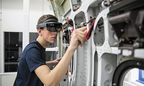 Un becario de Airbus muestra el uso de las gafas Microsoft Hololens para la instalación y el mantenimiento de componentes del avión, durante una demostración en las instalaciones de la compañía en Hamburgo, Alemania