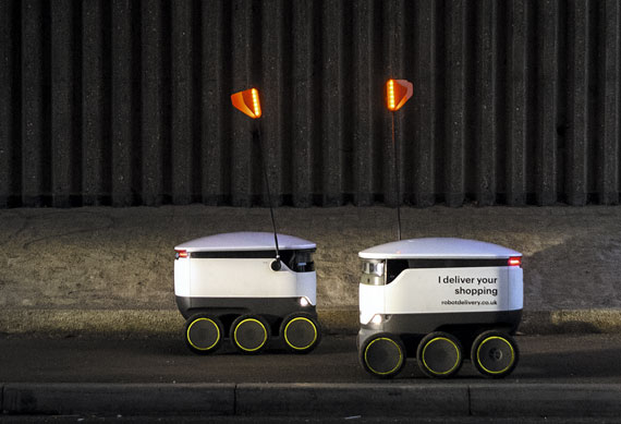 Two delivery robots developed by Starship, the company set up by two of the cofounders of Skype, pass on the pavement as they make home deliveries of groceries from a Co-op food store, Milton Keynes