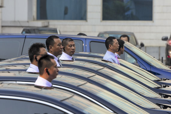 Drivers stand by cars on the day of the launch of Shouqi Limousine & Chauffeur, the first taxi-booking service authorized by the Chinese government, September 2015